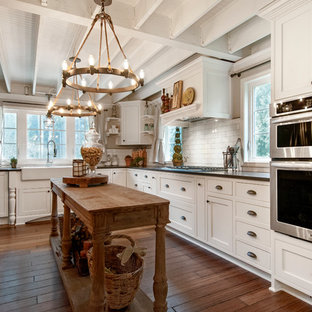 Photo of a country u-shaped eat-in kitchen in Seattle with a farmhouse sink, shaker cabinets, white cabinets, white splashback, subway tile splashback, stainless steel appliances, quartz benchtops, medium hardwood floors, an island and brown floor.