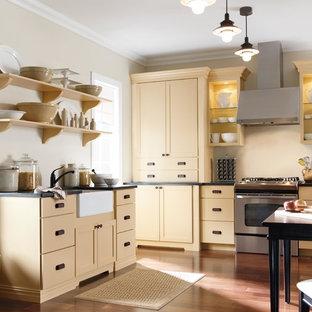 ニューヨークの中サイズのカントリー風おしゃれなキッチン (シェーカースタイル扉のキャビネット、黄色いキャビネット、シルバーの調理設備、無垢フローリング) の写真