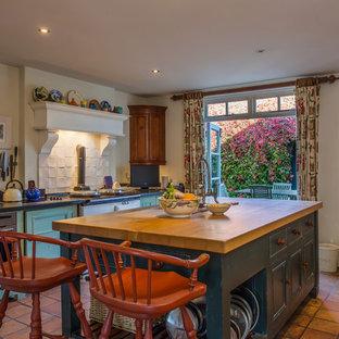 Foto de cocina de estilo de casa de campo con armarios con paneles empotrados, puertas de armario turquesas, salpicadero blanco, electrodomésticos blancos, suelo de baldosas de terracota y una isla