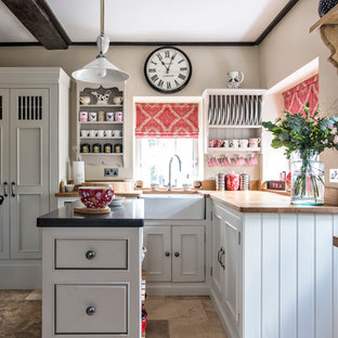 This is an example of a country l-shaped kitchen in Sussex with a farmhouse sink, beaded inset cabinets, white cabinets, wood benchtops and with island.