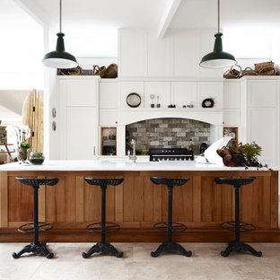Inspiration for a large country galley kitchen in Sydney with a farmhouse sink, shaker cabinets, white cabinets, quartz benchtops, grey splashback, stone tile splashback, black appliances, travertine floors, with island, grey floor and white benchtop.