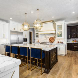 Idéer för ett stort klassiskt vit kök, med en rustik diskho, vita skåp, marmorbänkskiva, vitt stänkskydd, stänkskydd i marmor, rostfria vitvaror, ljust trägolv, flera köksöar, luckor med glaspanel och brunt golv