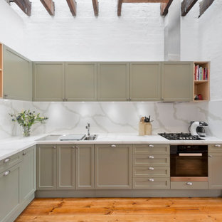 Mid-sized transitional l-shaped eat-in kitchen in Melbourne with a drop-in sink, shaker cabinets, green cabinets, quartz benchtops, white splashback, stone slab splashback, black appliances, medium hardwood floors, with island, brown floor and white benchtop.