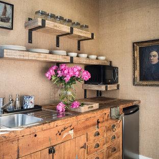 Foto di una piccola cucina eclettica con lavello da incasso, ante lisce, ante in legno scuro, top in legno, paraspruzzi marrone, elettrodomestici in acciaio inossidabile e pavimento in legno massello medio