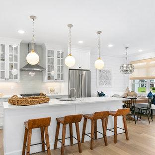 Esempio di una cucina chic con lavello sottopiano, ante in stile shaker, ante bianche, top in quarzo composito, elettrodomestici in acciaio inossidabile, un'isola, top bianco, parquet chiaro e pavimento blu