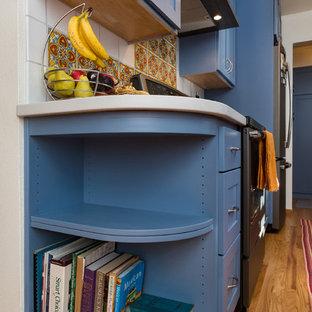 他の地域の小さいサンタフェスタイルのおしゃれなキッチン (エプロンフロントシンク、シェーカースタイル扉のキャビネット、青いキャビネット、クオーツストーンカウンター、オレンジのキッチンパネル、磁器タイルのキッチンパネル、シルバーの調理設備、濃色無垢フローリング、アイランドなし、白いキッチンカウンター) の写真