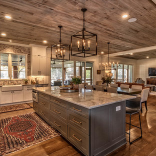 Photo of a country l-shaped kitchen in Other with a farmhouse sink, shaker cabinets, white cabinets, brick splashback, stainless steel appliances, dark hardwood floors, with island, brown floor and grey benchtop.