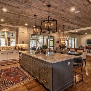 Rustikale Küche in L-Form mit Landhausspüle, Schrankfronten im Shaker-Stil, weißen Schränken, Rückwand aus Backstein, Küchengeräten aus Edelstahl, dunklem Holzboden, Kücheninsel, braunem Boden und grauer Arbeitsplatte in Sonstige