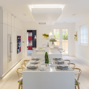 This is an example of a large contemporary open plan kitchen in Hampshire with flat-panel cabinets, yellow cabinets, composite countertops, black appliances, light hardwood flooring, an island, brown floors and yellow worktops.