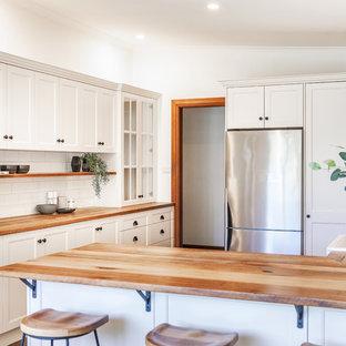 Inredning av ett lantligt mellanstort gul gult kök, med en rustik diskho, skåp i shakerstil, vita skåp, träbänkskiva, vitt stänkskydd, stänkskydd i tunnelbanekakel, svarta vitvaror, skiffergolv, en halv köksö och grått golv