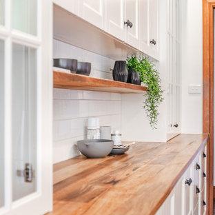Idéer för mellanstora lantliga gult kök, med en rustik diskho, skåp i shakerstil, vita skåp, träbänkskiva, vitt stänkskydd, stänkskydd i tunnelbanekakel, svarta vitvaror, skiffergolv, en halv köksö och grått golv