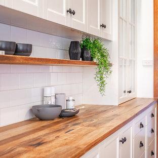 Неиссякаемый источник вдохновения для домашнего уюта: угловая кухня среднего размера в стиле кантри с обеденным столом, раковиной в стиле кантри, фасадами в стиле шейкер, белыми фасадами, деревянной столешницей, белым фартуком, фартуком из плитки кабанчик, черной техникой, полом из сланца, полуостровом, серым полом и желтой столешницей