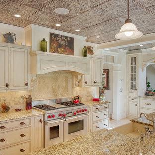 ボストンのヴィクトリアン調のおしゃれなアイランドキッチン (エプロンフロントシンク、インセット扉のキャビネット、ベージュのキャビネット、ベージュキッチンパネル、シルバーの調理設備) の写真