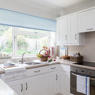 ロンドンの小さいカントリー風おしゃれなキッチン (シングルシンク、落し込みパネル扉のキャビネット、白いキャビネット、ラミネートカウンター、ベージュキッチンパネル、セラミックタイルのキッチンパネル、シルバーの調理設備の、リノリウムの床、アイランドなし) の写真