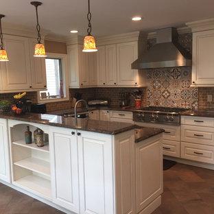 ニューヨークの中くらいのサンタフェスタイルのおしゃれなキッチン (アンダーカウンターシンク、レイズドパネル扉のキャビネット、白いキャビネット、御影石カウンター、茶色いキッチンパネル、テラコッタタイルのキッチンパネル、シルバーの調理設備、テラコッタタイルの床、茶色い床、茶色いキッチンカウンター) の写真
