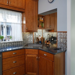 Photo of a small country u-shaped separate kitchen in Philadelphia with an undermount sink, recessed-panel cabinets, medium wood cabinets, quartz benchtops, metallic splashback, metal splashback, stainless steel appliances, porcelain floors and multi-coloured floor.