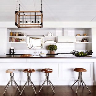 Inspiration for a large farmhouse galley dark wood floor open concept kitchen remodel in Melbourne with a farmhouse sink, shaker cabinets, white cabinets, wood countertops, white backsplash, ceramic backsplash, white appliances and an island