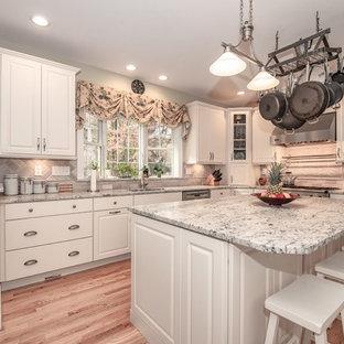 ニューヨークの大きいシャビーシック調のおしゃれなキッチン (ドロップインシンク、レイズドパネル扉のキャビネット、白いキャビネット、クオーツストーンカウンター、グレーのキッチンパネル、セラミックタイルのキッチンパネル、シルバーの調理設備の、無垢フローリング、茶色い床、グレーのキッチンカウンター) の写真