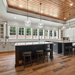 Large farmhouse u-shaped medium tone wood floor and brown floor kitchen photo in Atlanta with white cabinets, granite countertops, stainless steel appliances, two islands, a farmhouse sink, white backsplash, stone tile backsplash, gray countertops and shaker cabinets