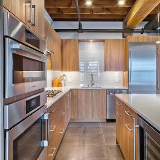 ミネアポリスの中くらいのインダストリアルスタイルのおしゃれなキッチン (アンダーカウンターシンク、フラットパネル扉のキャビネット、中間色木目調キャビネット、クオーツストーンカウンター、白いキッチンパネル、ガラスタイルのキッチンパネル、シルバーの調理設備、磁器タイルの床) の写真