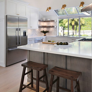 Photo of a large contemporary u-shaped kitchen/diner in Orange County with recessed-panel cabinets, white cabinets, engineered stone countertops, multi-coloured splashback, engineered quartz splashback, stainless steel appliances, a breakfast bar, yellow worktops, a submerged sink and beige floors.