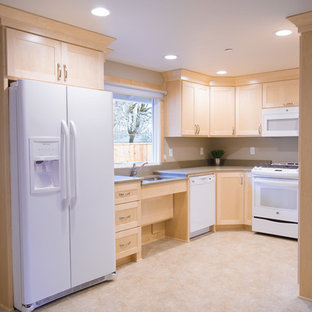 This is an example of a mid-sized transitional u-shaped separate kitchen in Portland with an undermount sink, shaker cabinets, light wood cabinets, quartz benchtops, white appliances, vinyl floors, no island, multi-coloured floor and grey benchtop.