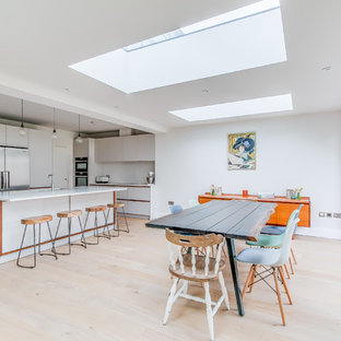 Medium sized contemporary l-shaped kitchen/diner in London with a submerged sink, flat-panel cabinets, white cabinets, composite countertops, white splashback, stainless steel appliances, an island, beige floors, light hardwood flooring and white worktops.