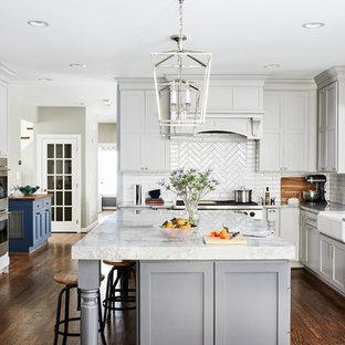 ワシントンD.C.の大きいトラディショナルスタイルのおしゃれなキッチン (エプロンフロントシンク、シェーカースタイル扉のキャビネット、グレーのキャビネット、珪岩カウンター、磁器タイルのキッチンパネル、シルバーの調理設備の、茶色い床、グレーのキッチンカウンター、白いキッチンパネル、濃色無垢フローリング) の写真