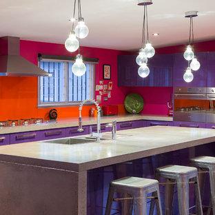 Immagine di una cucina contemporanea con ante lisce, elettrodomestici in acciaio inossidabile, paraspruzzi con lastra di vetro, lavello da incasso, paraspruzzi arancione e ante viola