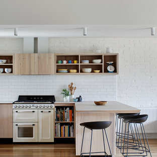 Inspiration for a mid-sized contemporary kitchen in Melbourne with a double-bowl sink, flat-panel cabinets, light wood cabinets, quartz benchtops, white splashback, porcelain splashback, white appliances, with island, beige benchtop, light hardwood floors and beige floor.