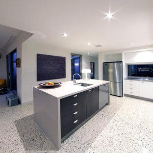 Foto de cocina comedor en L, contemporánea, grande, con fregadero bajoencimera, armarios con paneles lisos, puertas de armario negras, encimera de cuarzo compacto, salpicadero de vidrio, electrodomésticos de acero inoxidable, suelo de terrazo, una isla y suelo blanco
