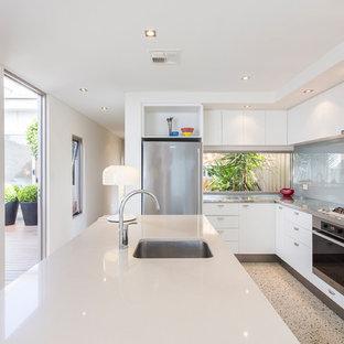 Создайте стильный интерьер: большая угловая кухня в современном стиле с обеденным столом, врезной раковиной, плоскими фасадами, черными фасадами, столешницей из кварцевого композита, серым фартуком, фартуком из стеклянной плитки, техникой из нержавеющей стали, полом из терраццо, островом и белым полом - последний тренд