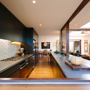Photo of a mid-sized contemporary u-shaped open plan kitchen in Sydney with an integrated sink, flat-panel cabinets, black cabinets, concrete benchtops, white splashback, medium hardwood floors and no island.