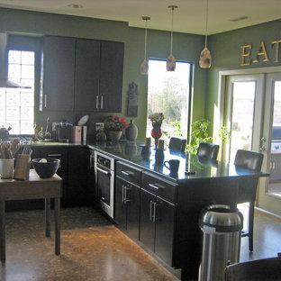 Moderne Küche mit flächenbündigen Schrankfronten, schwarzen Schränken, Granit-Arbeitsplatte, Rückwand aus Stein, Küchengeräten aus Edelstahl, Korkboden und Halbinsel in Sonstige