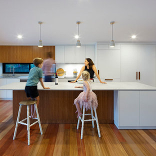 Design ideas for a mid-sized beach style kitchen in Brisbane with an undermount sink, granite benchtops, white splashback, medium hardwood floors, with island, grey benchtop, flat-panel cabinets and white cabinets.