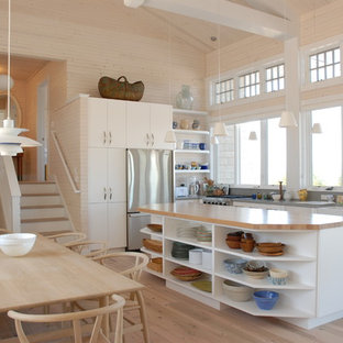 Inspiration for a coastal l-shaped light wood floor open concept kitchen remodel in Other with a farmhouse sink, flat-panel cabinets, white cabinets, stainless steel appliances and an island