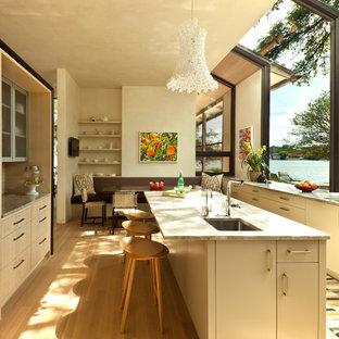 Idéer för att renovera ett funkis kök och matrum, med en undermonterad diskho, släta luckor och skåp i ljust trä