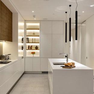 Bild på ett stort funkis vit vitt kök, med en dubbel diskho, släta luckor, vita skåp, bänkskiva i koppar, beige stänkskydd, glaspanel som stänkskydd, rostfria vitvaror, klinkergolv i keramik, en köksö och grått golv