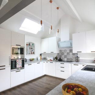 ウエストミッドランズの広いコンテンポラリースタイルのおしゃれなコの字型キッチン (ドロップインシンク、フラットパネル扉のキャビネット、白いキャビネット、グレーのキッチンパネル、パネルと同色の調理設備、アイランドなし、茶色い床、グレーのキッチンカウンター) の写真