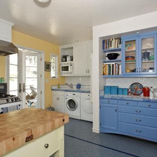 Modelo de cocina en L, tradicional, de tamaño medio, con despensa, armarios estilo shaker, puertas de armario azules, encimera de azulejos, salpicadero blanco, salpicadero de azulejos de cerámica, electrodomésticos blancos, suelo de terrazo, una isla y suelo azul