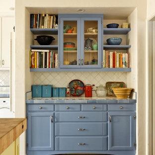 Diseño de cocina en L, tradicional, de tamaño medio, con despensa, armarios estilo shaker, puertas de armario azules, encimera de azulejos, salpicadero blanco, salpicadero de azulejos de cerámica, electrodomésticos blancos, suelo de terrazo, una isla y suelo azul