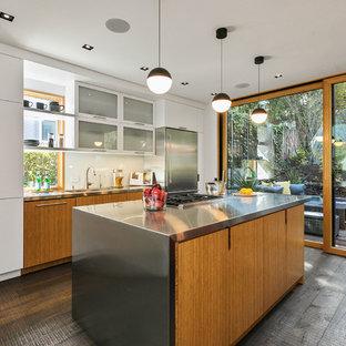 サンフランシスコのエクレクティックスタイルのおしゃれなキッチン (フラットパネル扉のキャビネット、中間色木目調キャビネット、ステンレスカウンター、白いキッチンパネル、石スラブのキッチンパネル、シルバーの調理設備、濃色無垢フローリング、茶色い床、グレーのキッチンカウンター、一体型シンク) の写真