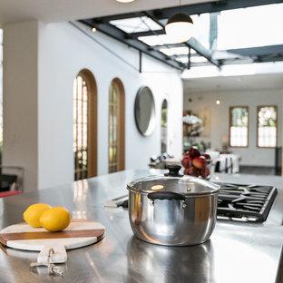 サンフランシスコのエクレクティックスタイルのおしゃれなアイランドキッチン (フラットパネル扉のキャビネット、中間色木目調キャビネット、ステンレスカウンター、白いキッチンパネル、グレーのキッチンカウンター、石スラブのキッチンパネル、シルバーの調理設備、濃色無垢フローリング、茶色い床、一体型シンク) の写真