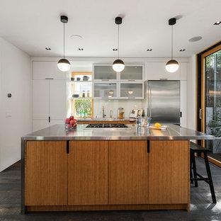 サンフランシスコのエクレクティックスタイルのおしゃれなキッチン (フラットパネル扉のキャビネット、中間色木目調キャビネット、ステンレスカウンター、白いキッチンパネル、石スラブのキッチンパネル、シルバーの調理設備の、濃色無垢フローリング、茶色い床、グレーのキッチンカウンター、一体型シンク) の写真