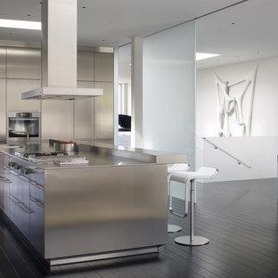 Foto de cocina contemporánea con encimera de acero inoxidable, puertas de armario en acero inoxidable, armarios con paneles lisos y electrodomésticos de acero inoxidable