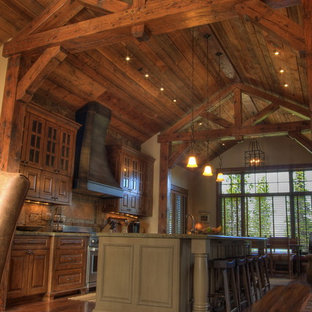 Eat-in kitchen - rustic galley eat-in kitchen idea in Other with raised-panel cabinets and medium tone wood cabinets