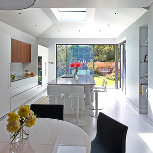 Mid-sized contemporary single-wall eat-in kitchen in London with flat-panel cabinets, solid surface benchtops, glass sheet splashback, painted wood floors, with island, white floor and beige benchtop.