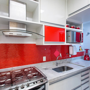 Small enclosed kitchen pictures - Small single-wall porcelain floor enclosed kitchen photo in Other with a single-bowl sink, flat-panel cabinets, white cabinets, red backsplash, glass tile backsplash, stainless steel appliances and no island