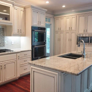 Inspiration for a mid-sized transitional l-shaped separate kitchen in Raleigh with a double-bowl sink, beaded inset cabinets, beige cabinets, granite benchtops, grey splashback, glass tile splashback, black appliances, dark hardwood floors, with island, red floor and beige benchtop.