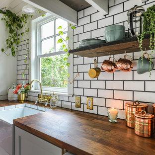 Einzeilige, Kleine Landhaus Küche ohne Insel mit weißen Schränken, Arbeitsplatte aus Holz, Küchenrückwand in Weiß, Rückwand aus Metrofliesen, dunklem Holzboden, braunem Boden, brauner Arbeitsplatte, Landhausspüle und Schrankfronten im Shaker-Stil in Portland